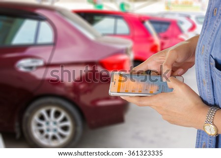 Girl use mobile phone, blur image of cars as background.