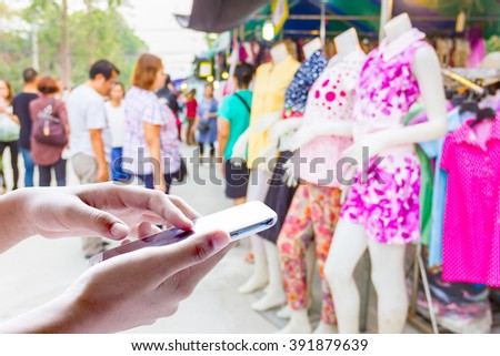 Girl use mobile phone, blur image of Clothing Thai style as background.