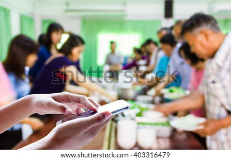 Girl use mobile phone, blur image of people	 put food into a dish as background.