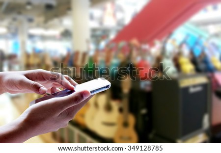 Girl use smart phone, blur image of musical instrument stores as background. - stock photo