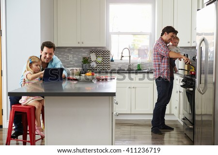 Girl uses tablet in kitchen with dad, while other dad cooks - stock photo