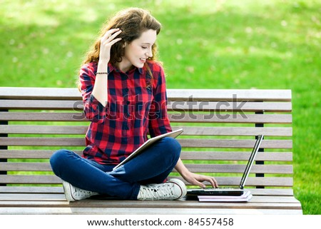 Girl using a laptop on a bench - stock photo