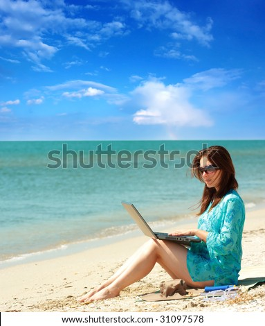 girl using a laptop on the beach
