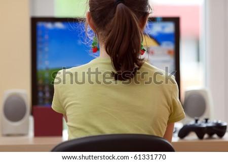 Girl using computer at home - stock photo
