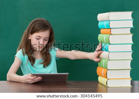 Girl Using Digital Tablet And Avoiding Stack Of Books At Desk In Classroom - stock photo