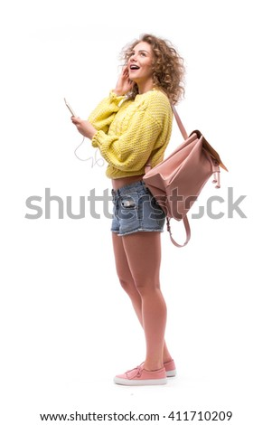 Girl  using earphones from smart phone, listening to music or talking to someone - stock photo
