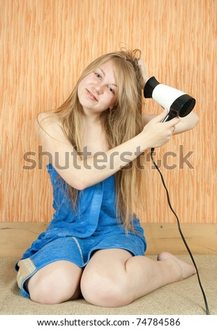 Girl using hairdryer in home interior - stock photo
