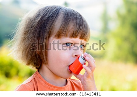 Girl Using Inhaler on a sunny day - to Treat Asthma Attack.  Inhalation treatment of respiratory diseases. Shallow depth of field. Allergy concept. - stock photo