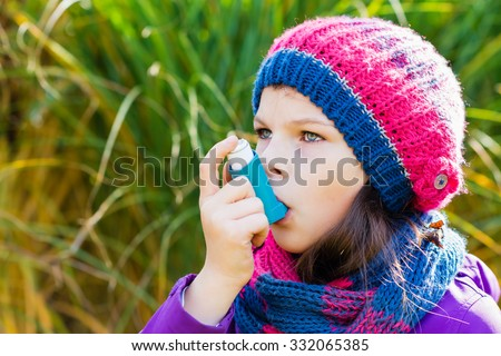 Girl Using Inhaler on an autumn day - to Treat Asthma Attack. Inhalation treatment of respiratory diseases. Shallow depth of field. Allergy concept. Asthma child - stock photo