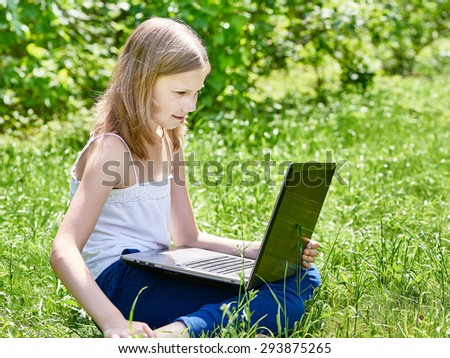 Girl using laptop on grass outdoor