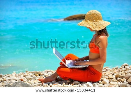 girl using laptop on the beach