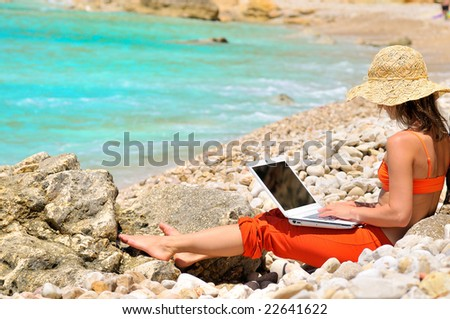 girl using laptop on the beach - stock photo
