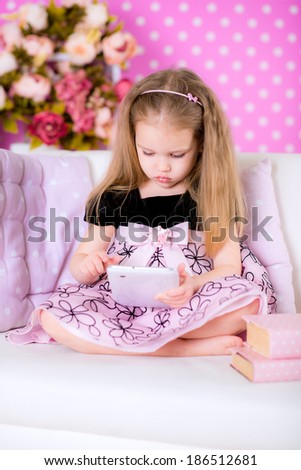 girl using modern tablet computers on white sofa in the polka-dot bright pink room at home fun game alone instead of reading book - stock photo
