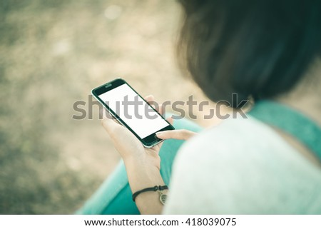 girl using smartphone outdoors. girl using phone in park.  woman using smartphone white screen. girl hand holding smartphone. beautiful woman using mobile phone. black color smartphone. vintage tone  - stock photo