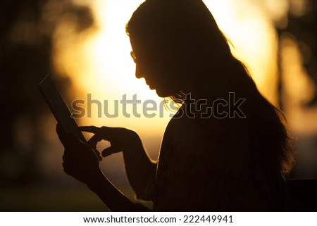 Girl Using Tablet At Sunset In Nature