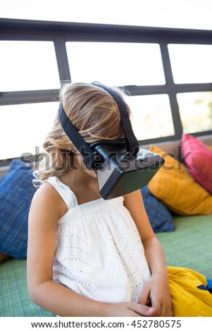 Girl using virtual reality headset while sitting on couch in school library - stock photo