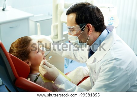 Girl visiting her dentist for teeth examination - stock photo