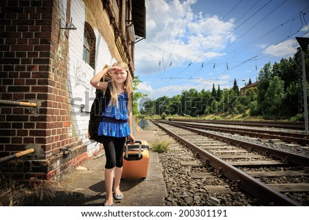 girl waiting for the train on the railway station - stock photo