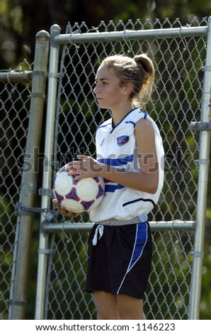 girl waiting on sideline to throw in soccer ball - stock photo