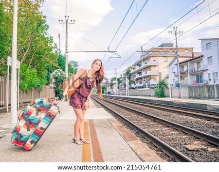 girl waiting the train at the station - stock photo