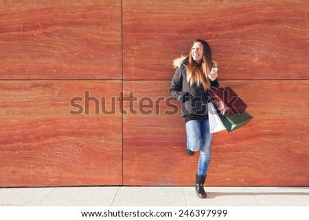 girl waits in front of a wall after shopping - stock photo