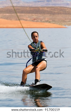 Girl wakeboarder enjoying water sports boarding behind a boat with beautiful Lake Powell in  the background at Glen Canyon National  Recreation Area, Utah, USA - stock photo