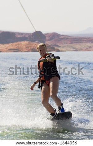 Girl wakeboarding at Lake Powell in Glen Canyon National Recreation Area Utah - stock photo