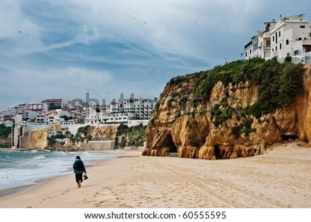 Girl waking on the Praia da Rocha at the Atlantic Ocean in Algarve, southern Portugal, in the morning - stock photo