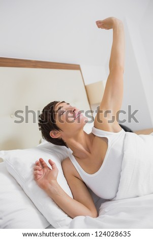 Girl waking up and stretching in hotel room - stock photo