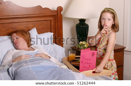 Girl waking up mother on Mothers Day