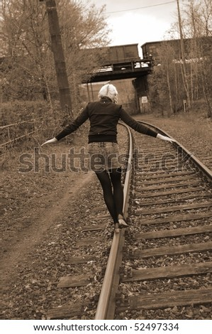 Girl walking along on rails - stock photo