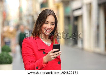 Girl walking and texting on the smart phone in the street wearing a red jacket in winter - stock photo