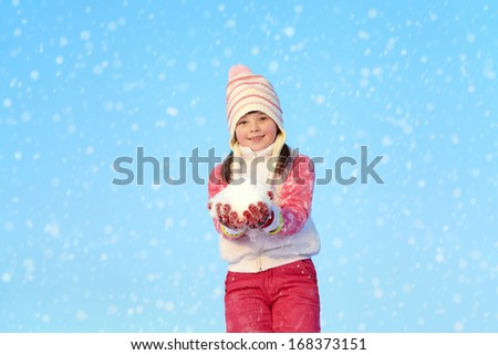 girl walking around outdoors in the winter, playing with snow - stock photo