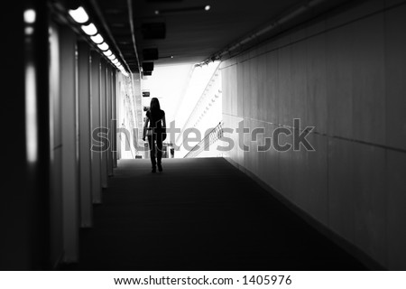 Girl walking down a long airport terminal hallway - stock photo
