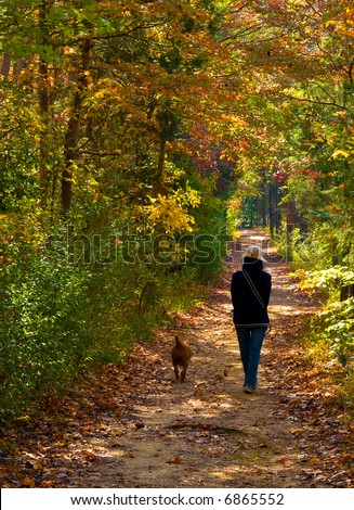 Girl walking her dog through the woods during fall - stock photo