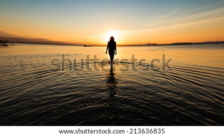 Girl Walking in Sunset by the sea - stock photo