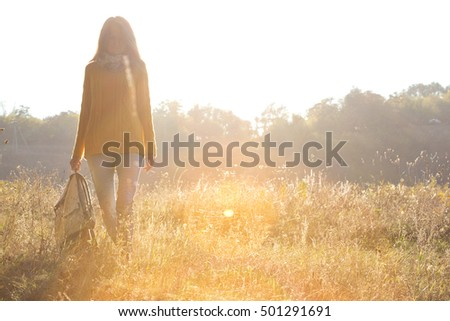 girl walking in the autumn forest at sunset light