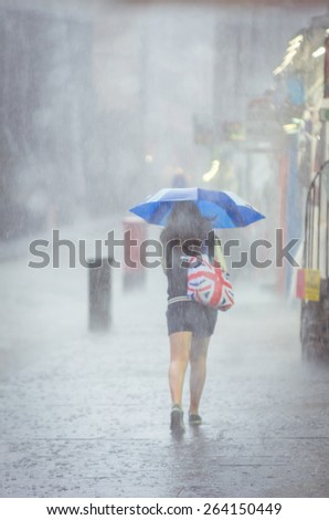 Girl walking in the rain with umbrella with bag with Britain flag print - stock photo