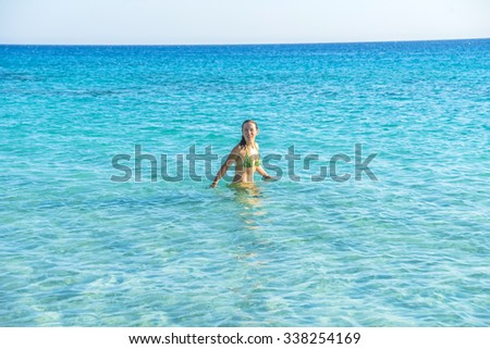 Girl walking in the water, on one of the most beautiful beaches in the world in Crete, Greece. - stock photo