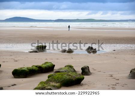 girl walking near unusual mud banks at Beal beach in county Kerry Ireland on the wild Atlantic way - stock photo
