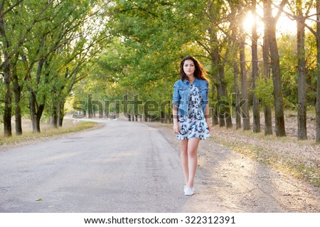 girl walking on a countryside road at sunset - stock photo