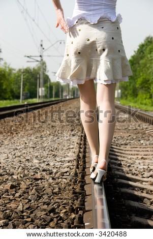 Girl walking on a railway. - stock photo