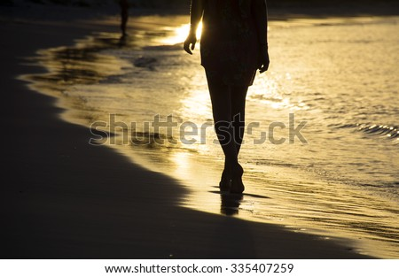 Girl walking on ocean beach at sunset - stock photo