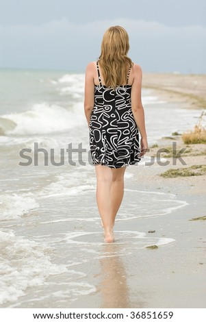 Girl walking on sand and waves, on the wild beach.