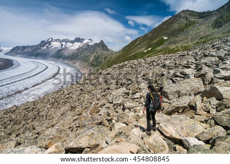 Girl walking on spectacular mountain scenery, Aletcsh glacier in background, Alps, Switzerland.