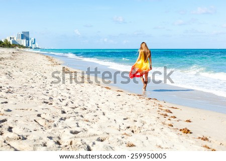 girl walking on the beach and enjoy amazing ocean view - stock photo