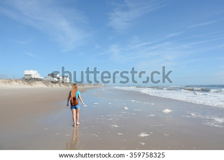 Girl walking on the beach with backpack, North Topsail Beach, North Carolina.