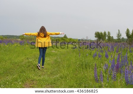 Girl walking on the field with blooming lupine.Shooting in the rain in the Moscow region. - stock photo