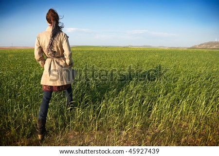 girl walking through a field of winter wheat - stock photo