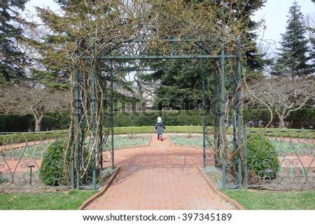 girl walking through archway on garden path - stock photo